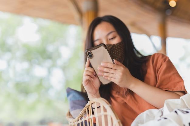 Vrouw in gezichtsmasker met behulp van haar mobiele telefoon zittend in een stoel.