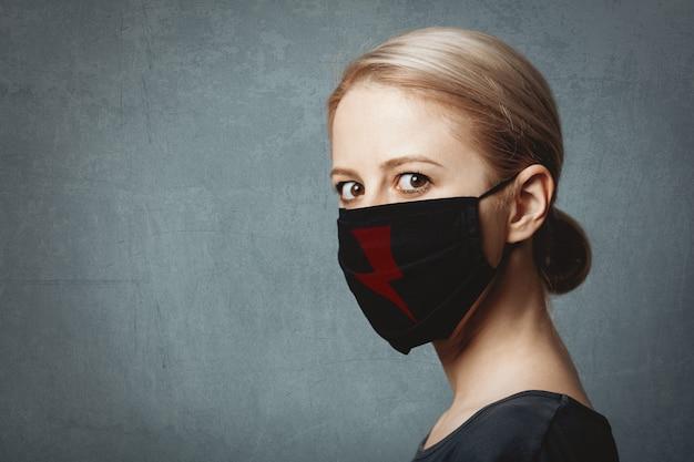 Vrouw in gezichtsmasker met symbool van vrouwelijk protest in polen