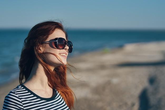 Vrouw in glazen en in een gestreept t-shirt bij zonsondergang of daar vlakbij het uitzicht op zee vanaf het balkon