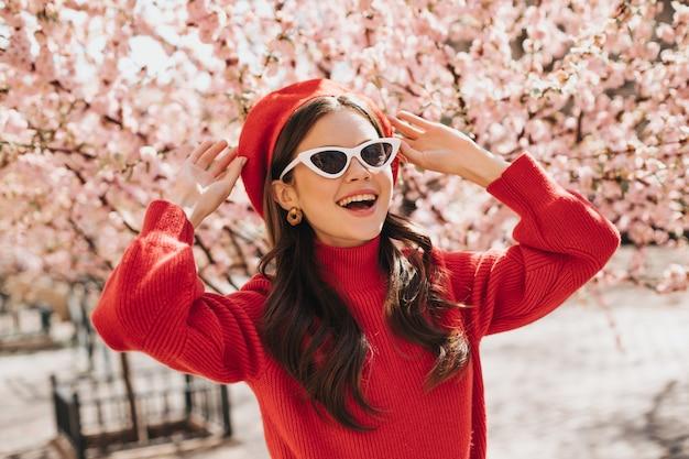 Vrouw in glazen en rode baret geniet van bloei van sakura. dame in cashemere trui glimlachen. portret van brunette buiten