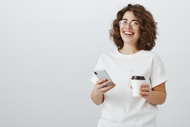 Vrouw in glazen glimlachend op mobiele telefoon sms-bericht, koffie drinken in kantoorpauze