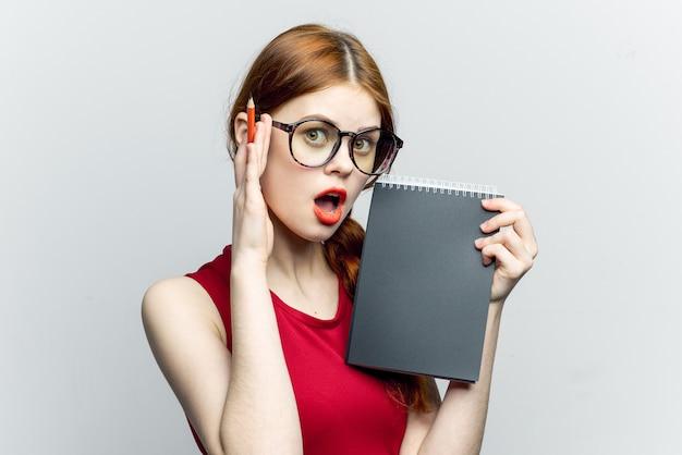 Vrouw in glazen met een notebook en pen, student
