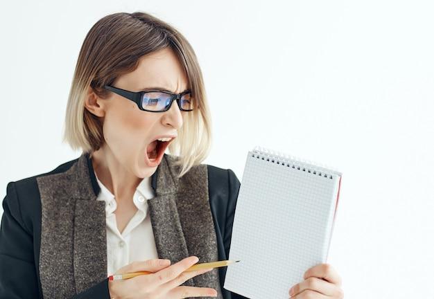 Vrouw in glazen met notitieblok in handen kantoor lichte achtergrond