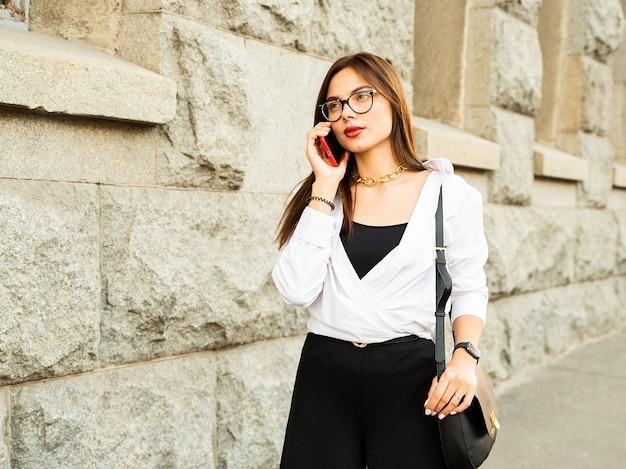 Vrouw in glazen praten aan de telefoon in de buurt van haar werkplek.
