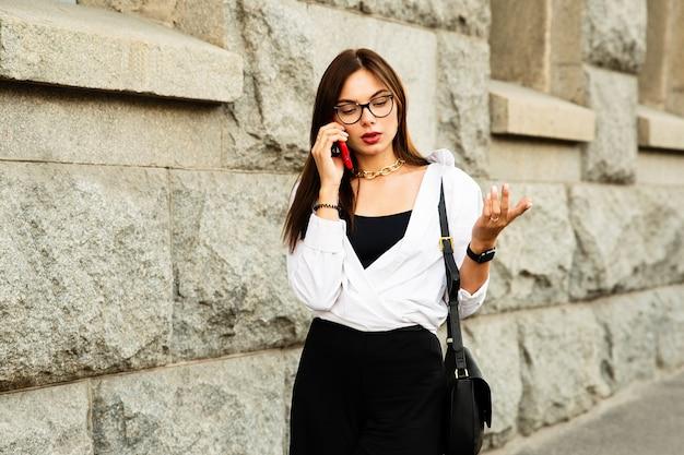 Vrouw in glazen praten aan de telefoon. ze ziet er gespannen uit en iets maakt haar van streek tijdens het telefoontje.