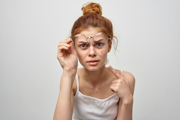 Vrouw in glazen toont een vinger aan een rood puistje op haar gezicht