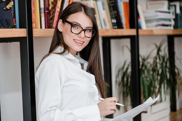 Vrouw in glazen werkt op kantoor met documenten en glimlachen