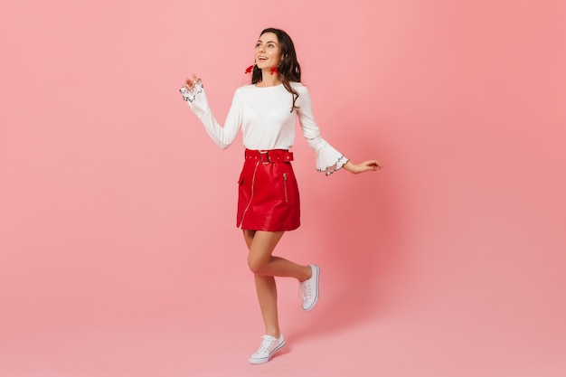 Vrouw in goed humeur loopt tegen roze achtergrond en kijkt bewonderend naar boven. dame in stijlvolle lederen rok glimlachen.