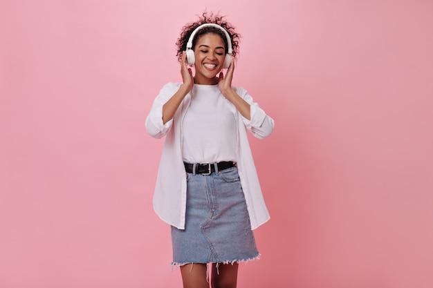 Vrouw in goed humeur luistert naar muziek met koptelefoon op roze muur