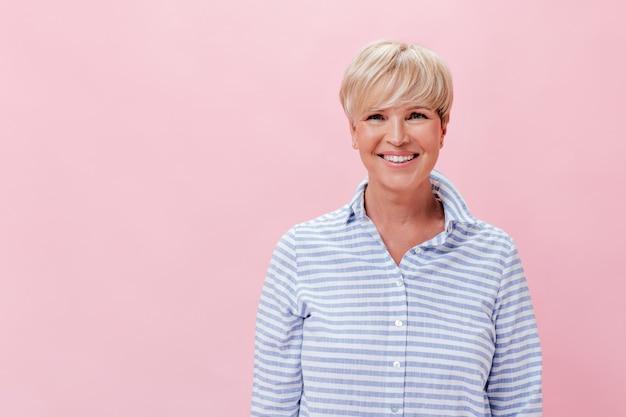 Vrouw in goed humeur onderzoekt camera met glimlach op roze achtergrond