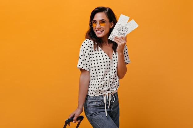 Vrouw in goed humeur vormt met kaartjes voor het vliegtuig en houdt koffer