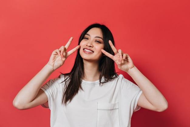 Vrouw in goed humeur vormt op de rode muur en vredesteken vertoont
