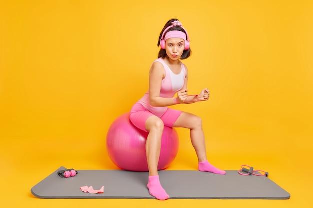 Vrouw in goede fysieke vorm traint handen met weerstandsband zit op fitnessbal luistert favoriete muziek via koptelefoon gekleed in sportkleding geïsoleerd op geel