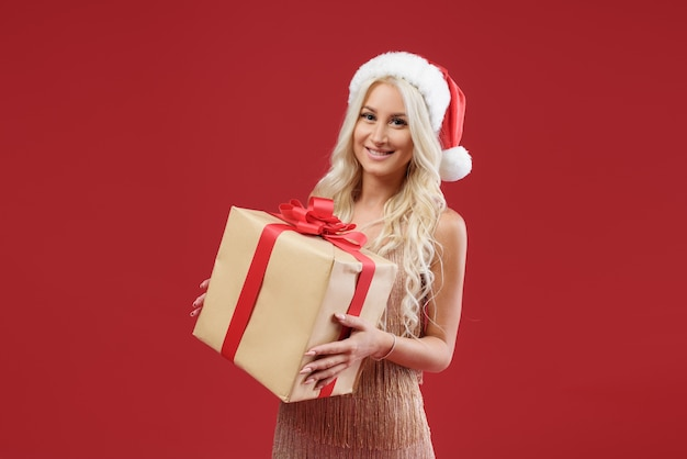Vrouw in gouden jurk en kerstmuts met een geschenkdoos op de rode muur
