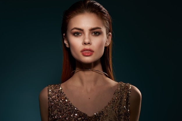 Vrouw in gouden jurk en oorbellen sieraden glamour model
