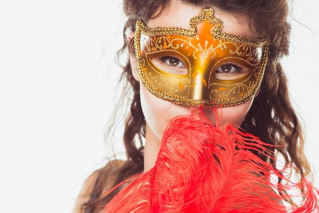 Vrouw in gouden masker met rode veren