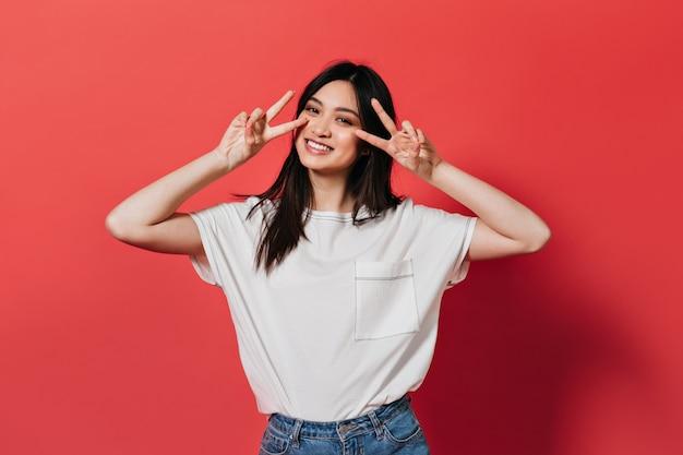 Vrouw in gratis t-shirt glimlacht en toont vredesteken op rode muur