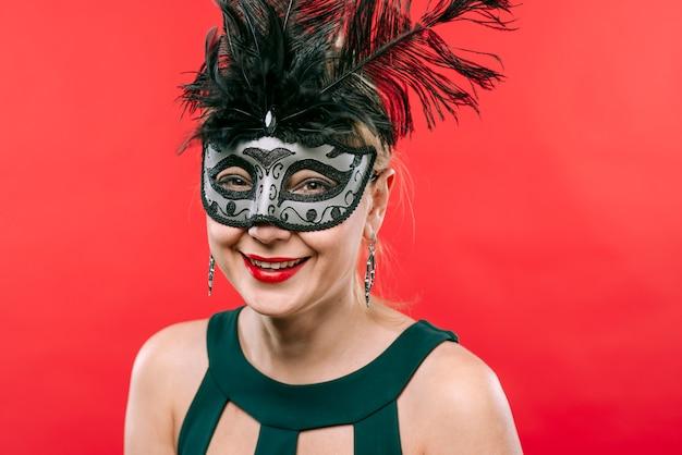 Vrouw in grijs masker met veren lachen