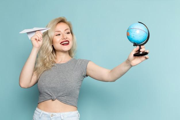 Vrouw in grijs shirt en heldere blauwe spijkerbroek holdign papieren vliegtuigje en kleine wereldbol
