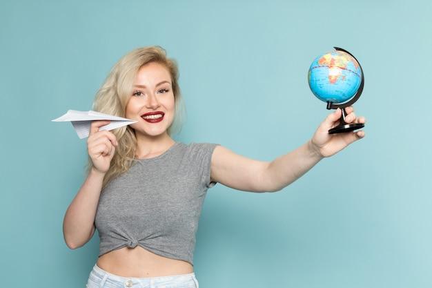 Vrouw in grijs shirt en heldere blauwe spijkerbroek met papieren vliegtuigje en kleine wereldbol