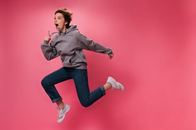 Vrouw in grijze hoodie en spijkerbroek springt op roze achtergrond. emotionele tiener meisje in sweatshirt en denim broek beweegt op geïsoleerde