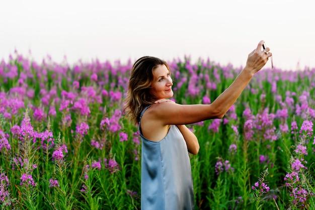 Vrouw in grijze jurk neemt selfie foto op mobiel op wilgenroosje weide