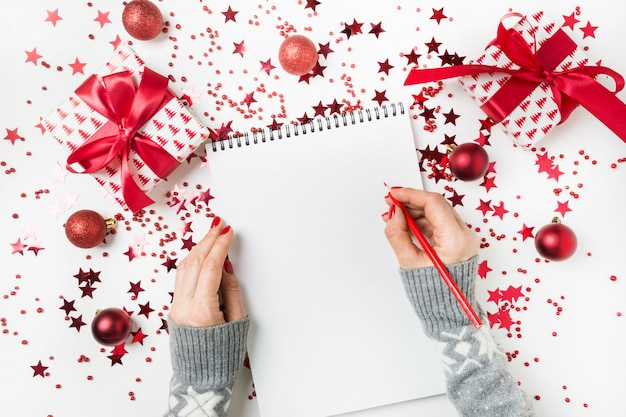 Vrouw in grijze sweater het schrijven controlelijst van plannen en dromen voor volgend jaar. wensenlijst voor kerstmis. takenlijst voor nieuw 2020-jaar met rood vakantiedecor.