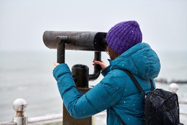 Vrouw in groen donsjack die in de winter naar zee kijkt door een verrekijker die op munten werkt. toerisme en sightseeing concept.