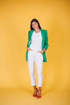 Vrouw in groen jasje in studio op gele achtergrond