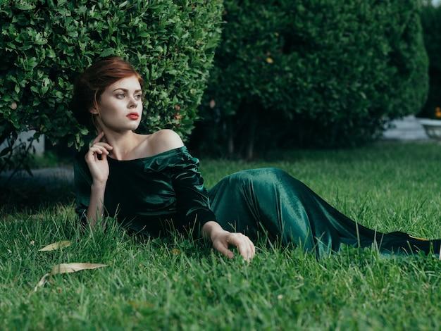 Vrouw in groene jurk ligt op het gras natuur luxe gotische prinses.