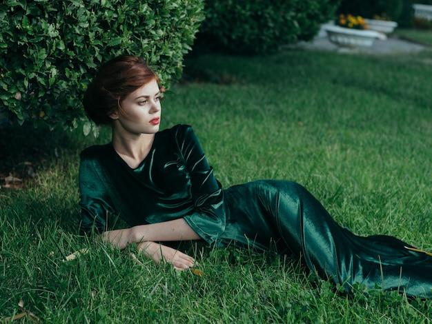 Vrouw in groene jurk ligt op het gras natuur luxe gotische prinses