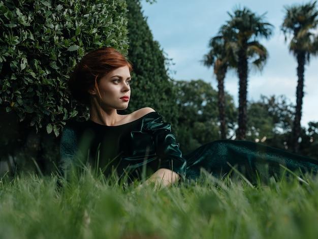 Vrouw in groene jurk ligt op het gras van de natuur en luxe diermodel