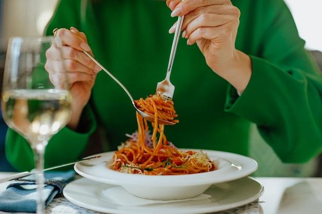 Vrouw in groene jurk na de lunch met glas witte wijn en verse spaghetti met zeevruchten. de nadruk ligt op spaghetti.