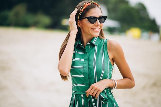 Vrouw in groene jurk op het strand