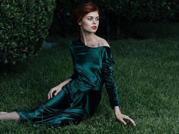 Vrouw in groene jurk zit op het gras natuur frisse lucht charme