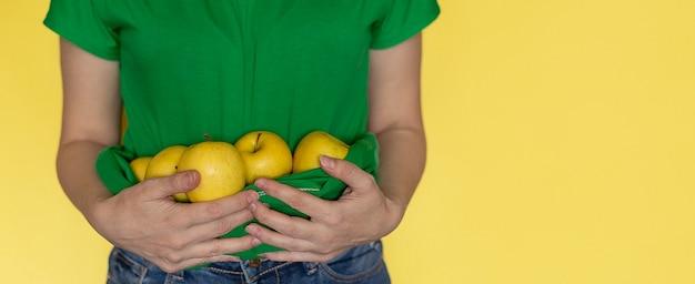 Vrouw in groene t-shirt houdt appel in handen op geel