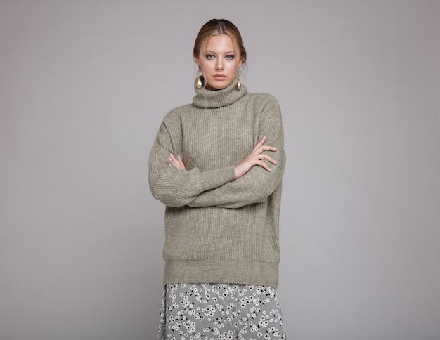 Vrouw in groene trui lange rok patronen op grijze achtergrond studio opname monochrome kleuren