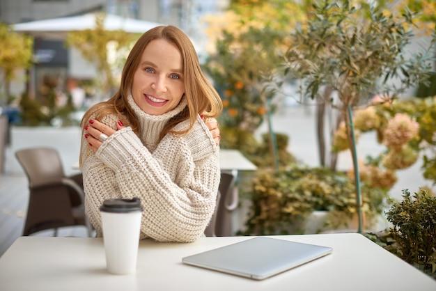 Vrouw in grof gebreide trui drinkt koffie en warmt zich op in het stadscafé. warme tinten horizontale foto