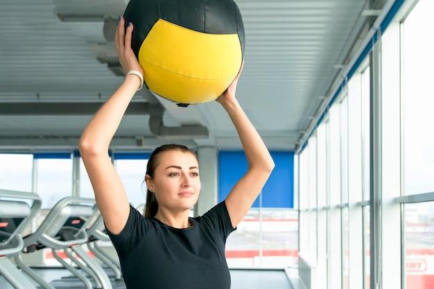 Vrouw in gymnastiek het ontspannen met geneeskundebal