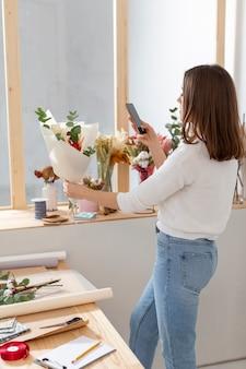 Vrouw in haar bloemenwinkel die foto's van bloemen neemt
