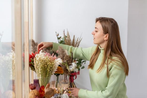 Vrouw in haar bloemenwinkel en bloemen