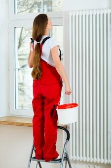 Vrouw in haar en huis dat vernieuwt schildert