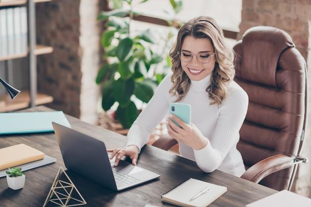 Vrouw in haar kantoor dat op laptop en telefoon werkt