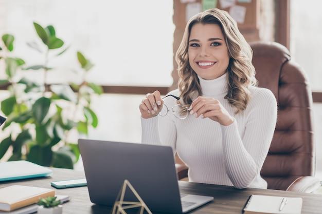 Vrouw in haar kantoor die op laptop werkt Premium Foto