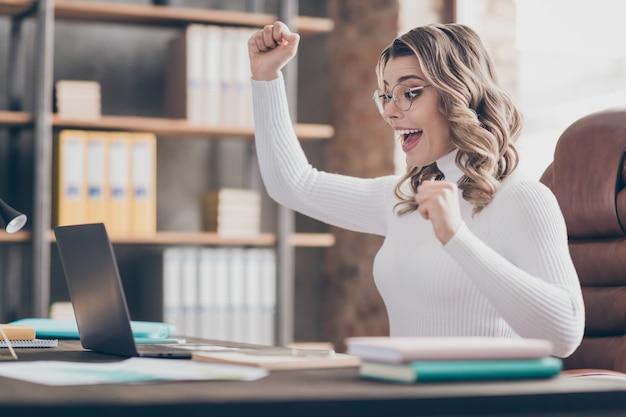 Vrouw in haar kantoor die op laptop werkt