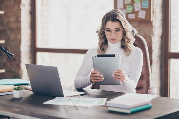 Vrouw in haar kantoor die op tablet werkt