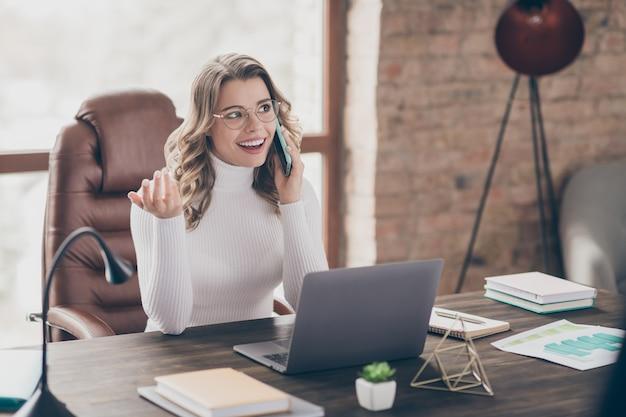 Vrouw in haar kantoor spreken over de telefoon
