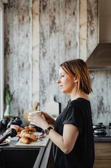 Vrouw in haar keuken met een kopje koffie