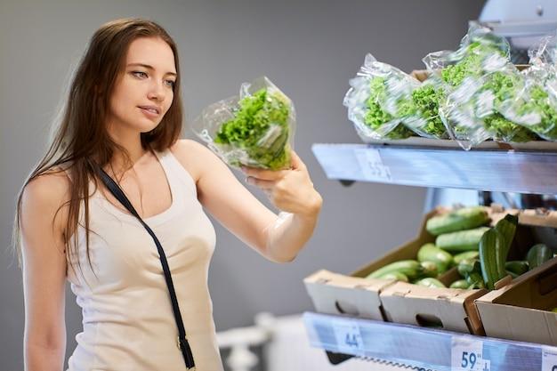Vrouw in haar s kiest salade in supermarkt