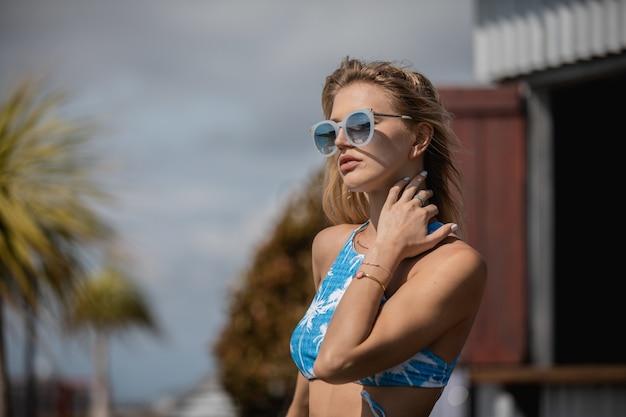 Vrouw in haar zwemkleding en zonnebril overdag